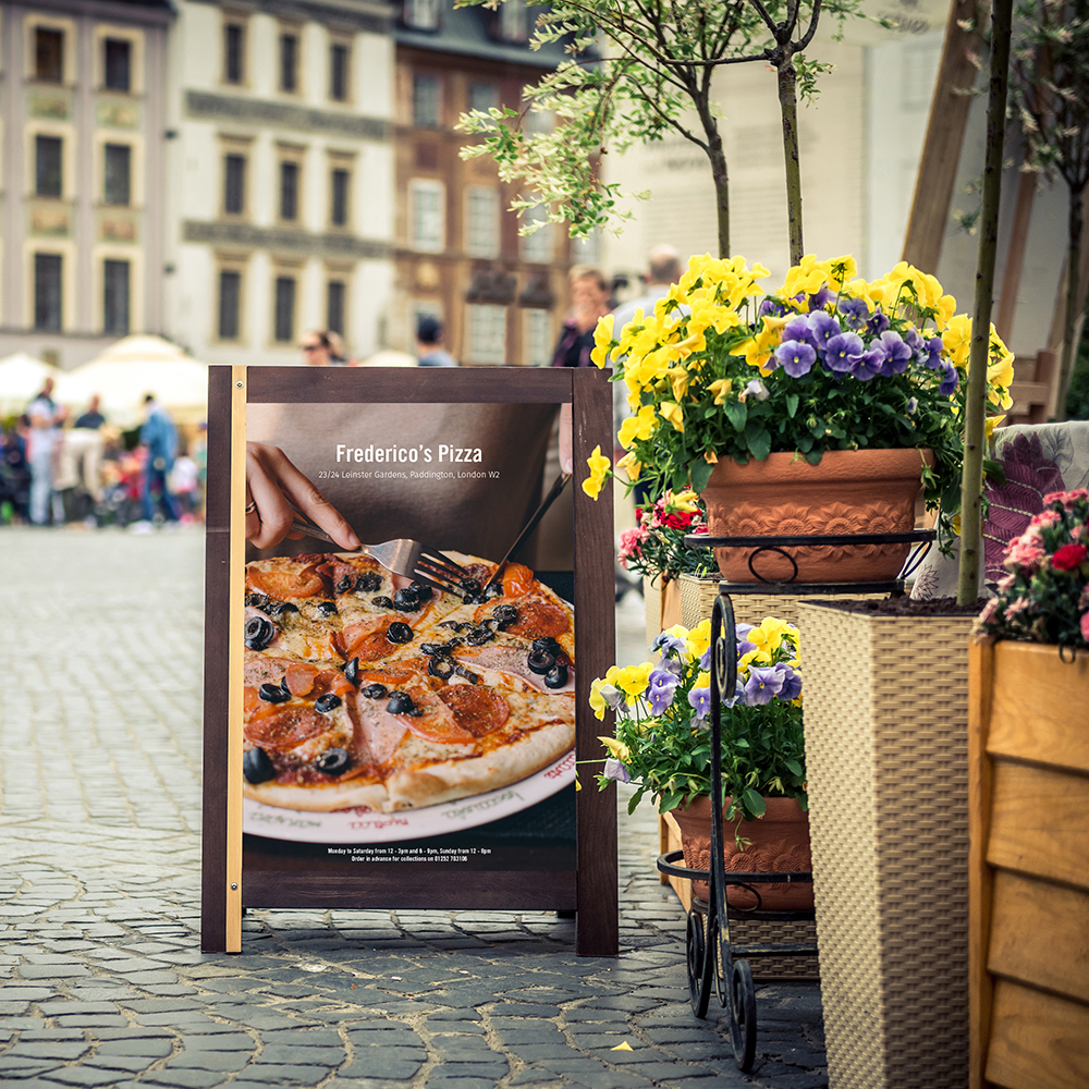 a picture of an outdoor display for a pizza restaurant next to flowers on a street
